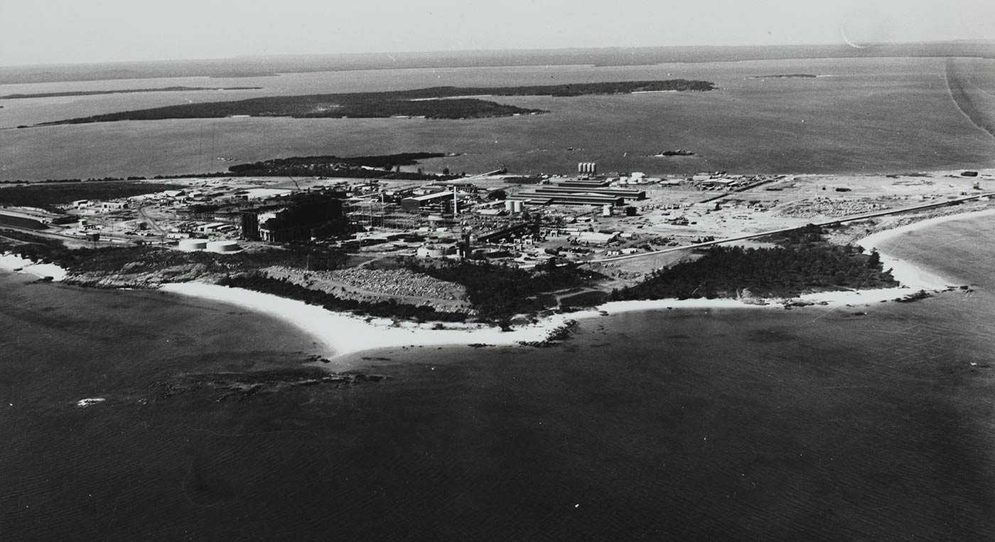 Black and white photo of an aerial view of a mining facility surrounded by natural landscape.