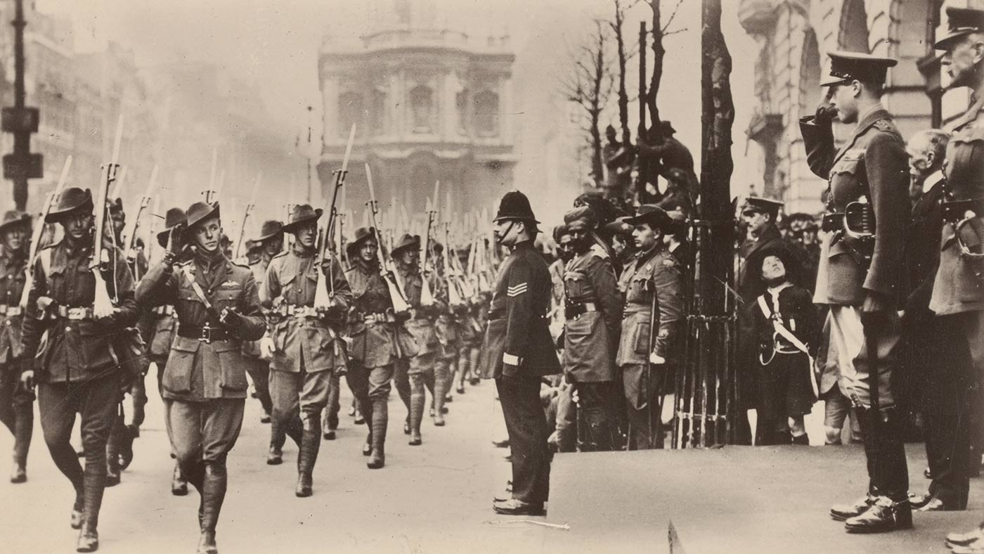 A postcard featuring a black and white photograph of soldiers marching along a street. To the right is a man dressed in military uniform saluting the soldiers. Printed text underneath the image reads