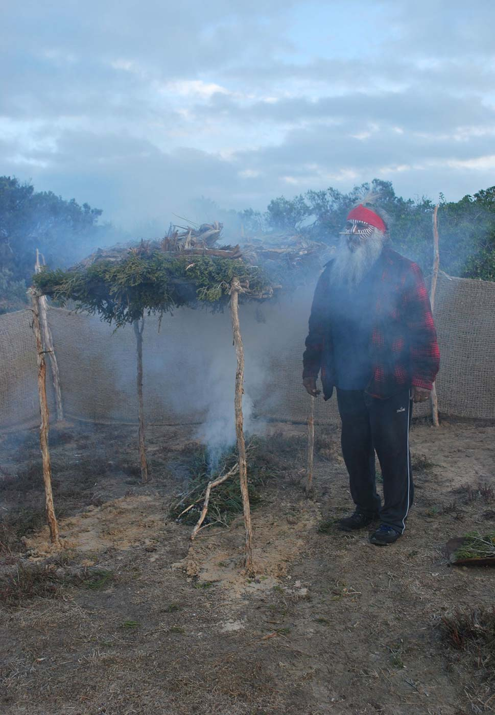 Photo of a man with face paint and bandana taking part in a smoking ritual.