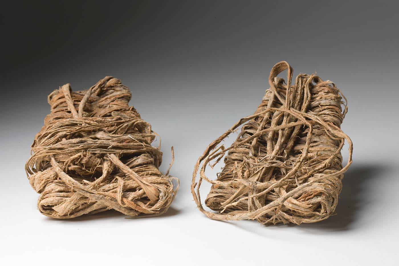 A pair of sandals made of plant fibre. They have a trapezoid shape and are made from strips of bark wrapped around and layered on top of each other. - click to view larger image