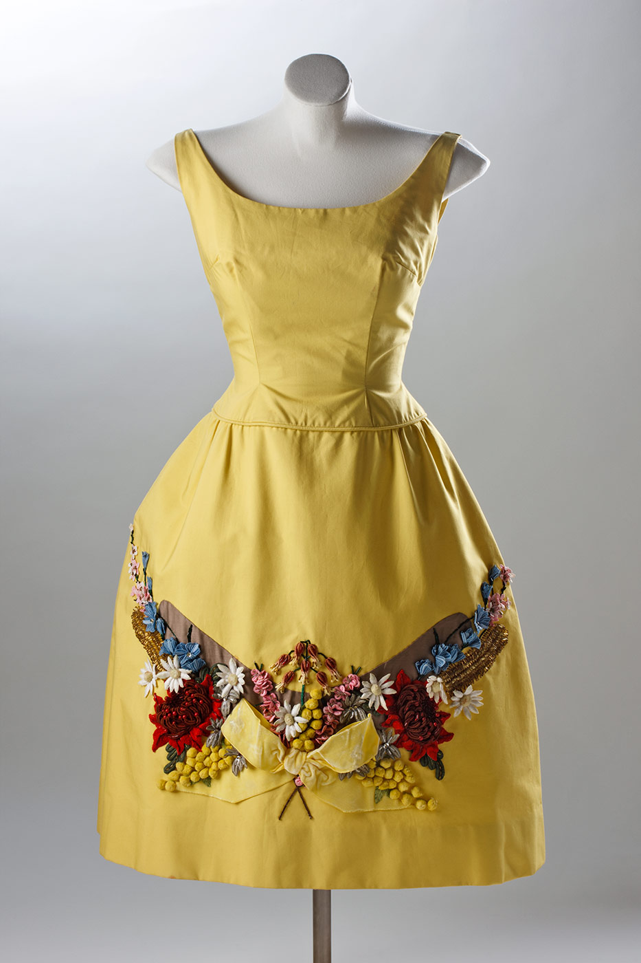 A knee length, golden yellow poplin dress with sleeveless bodice and an A-line, slightly gathered, skirt. The skirt features, on the front lower section, a heavy relief applique of material and beads featuring a richly textured and coloured design of Australian flora including wattle, waratah, banksia, and flannel flowers, over a boomerang shape. - click to view larger image