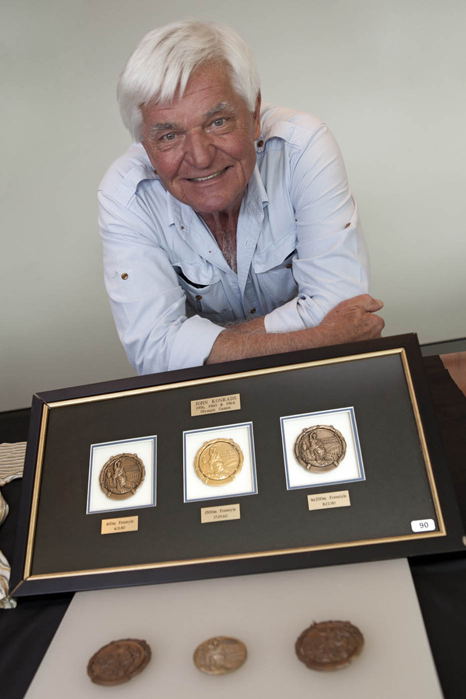 Colour photograph of a man resting with folded arms on a table. In front is a framed set of three circular medals. Another three medals are in the foreground. - click to view larger image