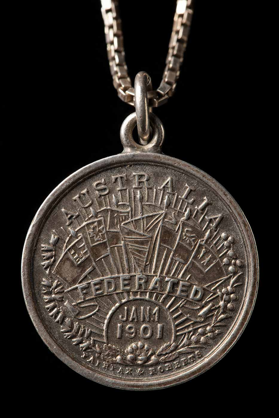 A silver circular double sided medal on a silver chain. The front face of the medal shows a display of flags set amongst the text 'AUSTRALIA / FEDERATED / JAN1 / 1901'. The scene is enclosed on the left by a bough of wheat and to the right by a branch of wattle. Below that is the embossed name 'FAIRFAX & ROBERT'. The reverse face of the medal shows two female figures exhanging items below a flying cherub or angel. The one on the right represents Britannia who holds out a scroll to the figure on the left. This female figure is holding a waratah flower and another scroll in her right hand and wears a flag of stars as a skirt. - click to view larger image