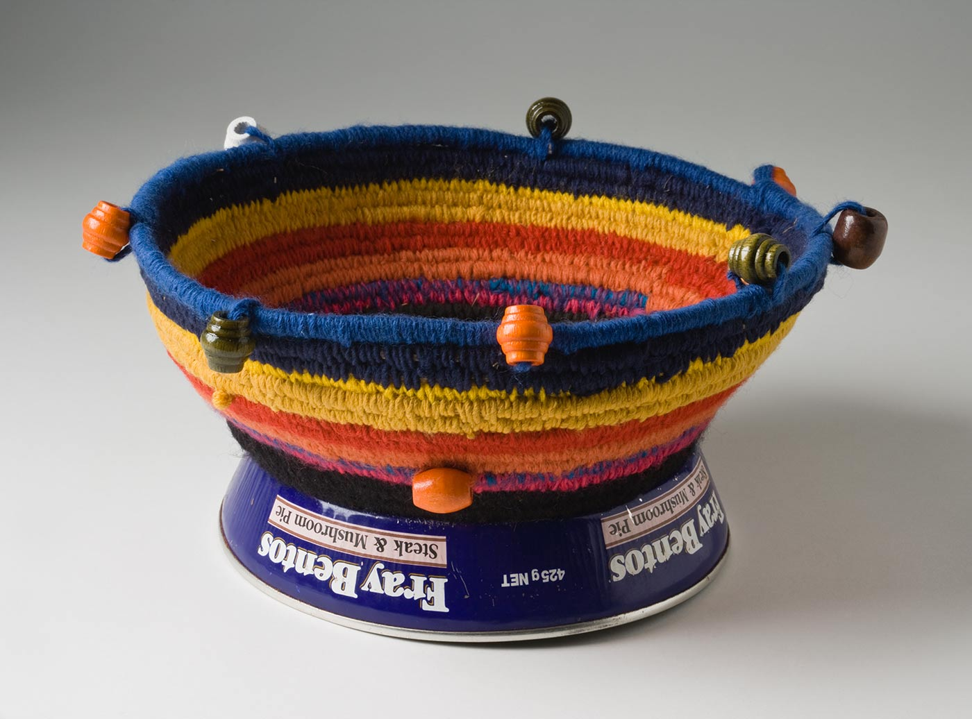 A circular coiled multicoloured yarn and plant fibre basket with a metal base and bead decoration. The base is made of a blue metal 'Fray Bento / Steak and Mushroom Pie' tin with sides, that is placed upside down. The yarn section is attached by black yarn threaded through holes punched in the metal. The closely coiled yarn is in stripes starting with blue at the top edge then yellow, red, orange, pink and black. The top edge and sides have a decoration of evenly spaced carved cylindrical wooden beads in orange, brown, green and white. - click to view larger image