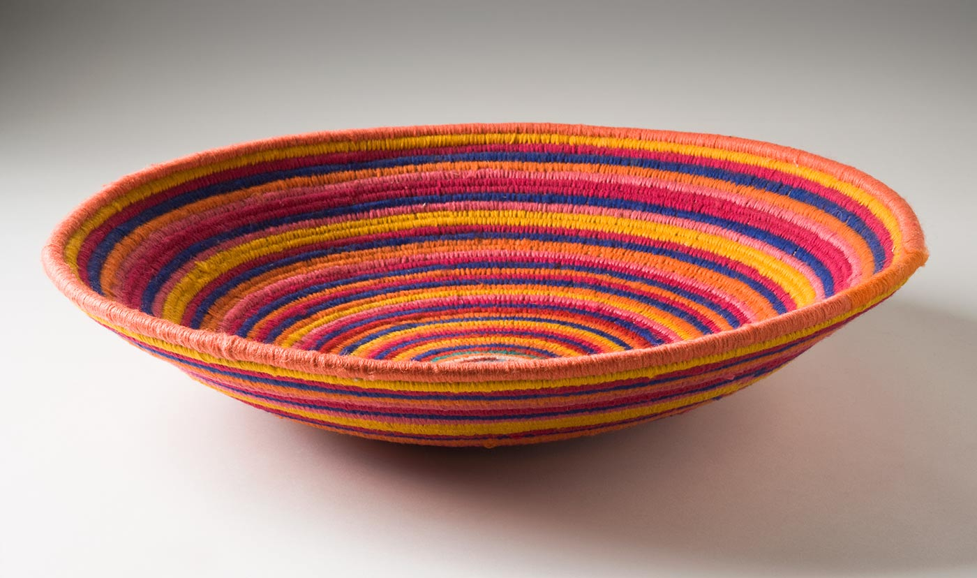 A multi-coloured circular coiled bowl-shaped basket made of yarn and plant fibre. The centre of the basket is in turquoise yarn followed by horizontal stripes of yarn in orange, blue, yellow, dark pink, red, green, brown, and pale pink. - click to view larger image