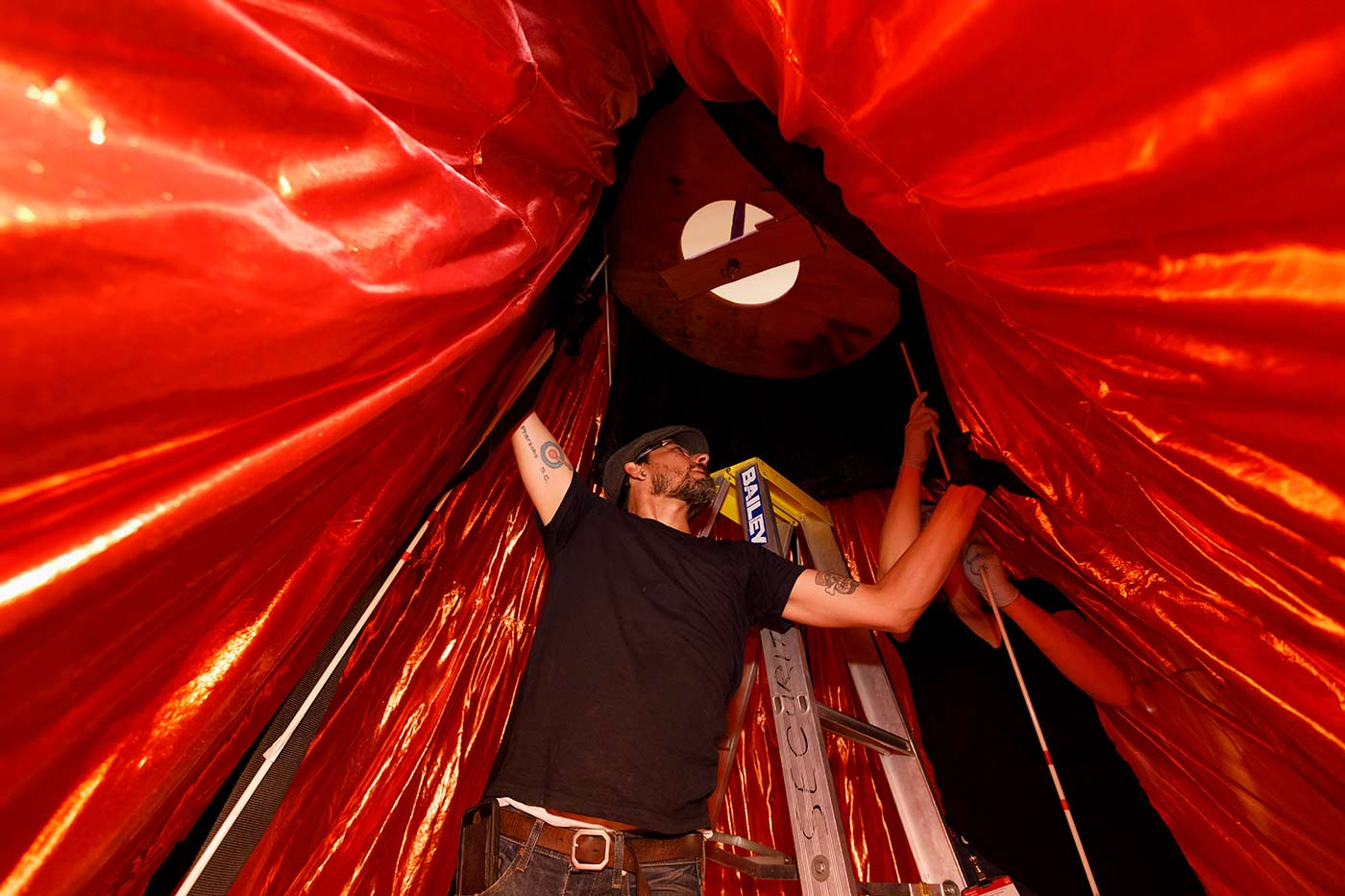 Colour photo of a man and a woman working on the interior of a large object constructed from red fabric mounted on a frame. - click to view larger image