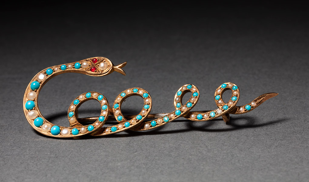 A brooch in the shape of a snake, with its body spelling 'Cooee'. It is decorated with white and blue-green stones and a two red eyes. - click to view larger image