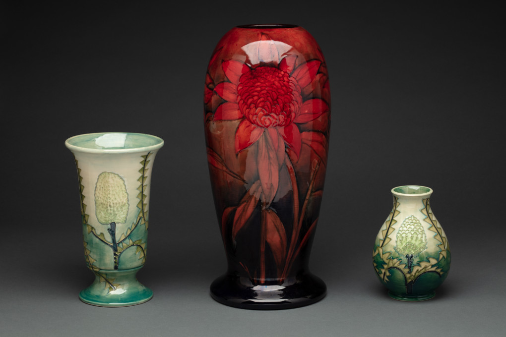 Three vases. The tallest, at centre, has a picture of a waratah on it and is glazed a deep red. Either side are two pale green vases with images of banksia plants and leaves.  - click to view larger image