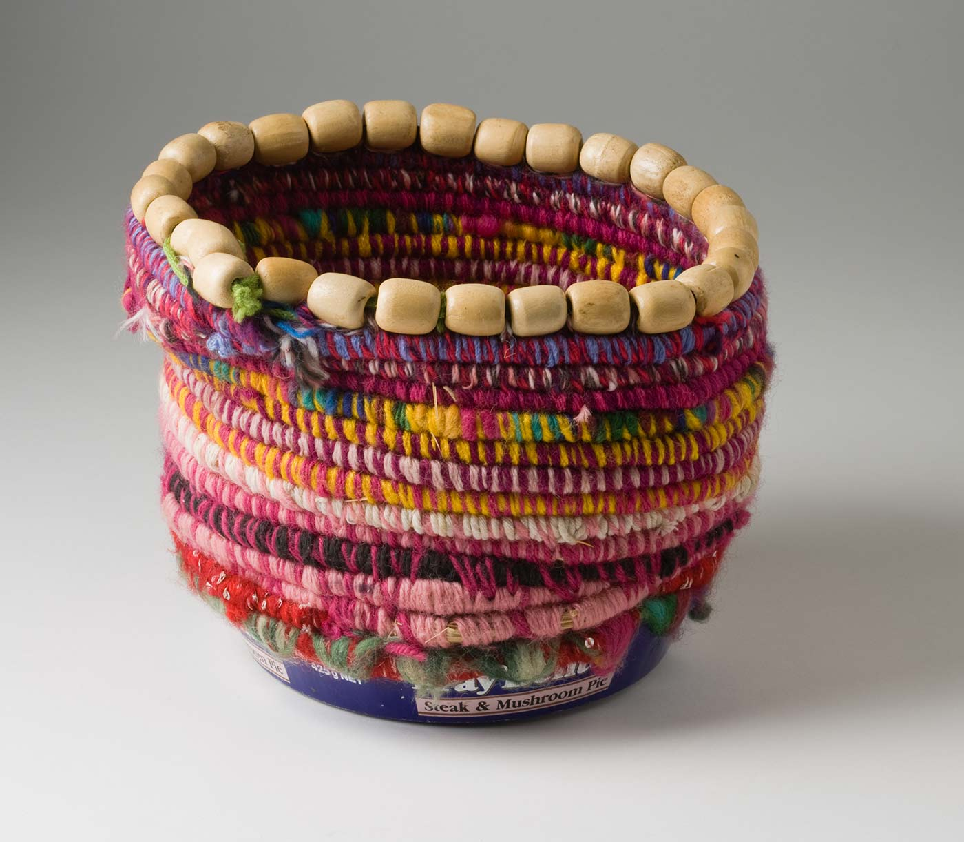 A non-symmetrical cylindrical coiled multicoloured yarn and plant fibre basket, with beaded top edge and metal container base. The blue and white circular base has 'Fray Bentos / Steak and Mushroom Pie' plus other text printed on it. The yarn and fibre section of the basket is attached to the metal base by yarn threaded through holes that have punched in the sides of the tin. The coiled yarn is rainbow coloured with a dominant dark pink tone. On the inside there are two carved brown cylinder beads, two red cylinder beads, one large green round bead and two small round beads in orange and brown. At the top edge of the basket is a ring of natural wood cylinder beads that have been attached with a green yarn. - click to view larger image