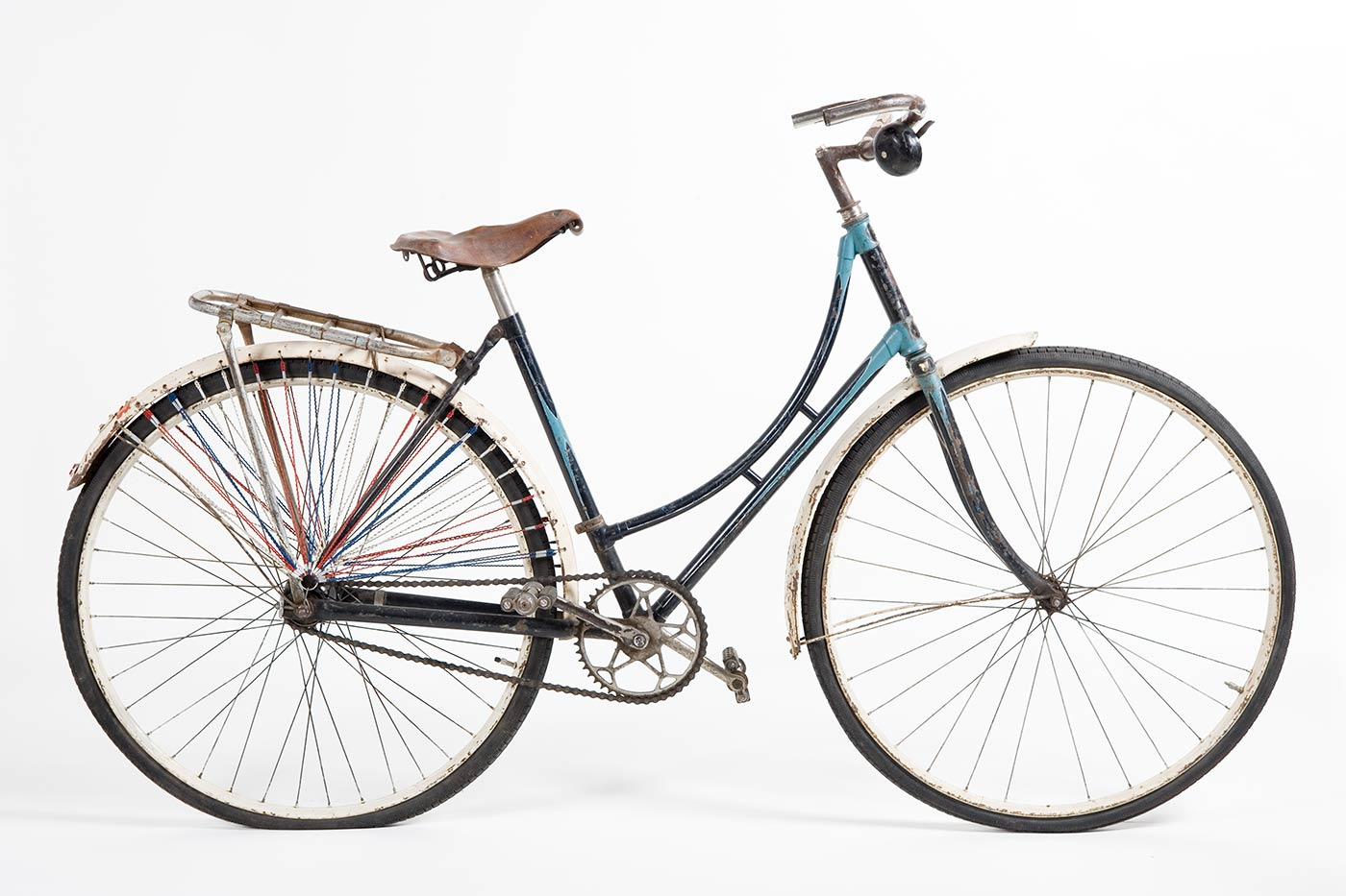 Ladies refurbished 'Roadmaster' bicycle. The frame is handpainted in turquoise and navy blue enamel paint, and the mudguards are white. It has a brown leather seat and a silver rack attached to the rear end. Both of the wheels are from a Malvern Star. The rear wheel has lengths of red, white and blue fine cord attached through the mudguard and gathering just above the centre of the wheel; on both sides of the rear wheel. Small reflector on rear wheel guard. Large black bell on right side of the handlebar. - click to view larger image