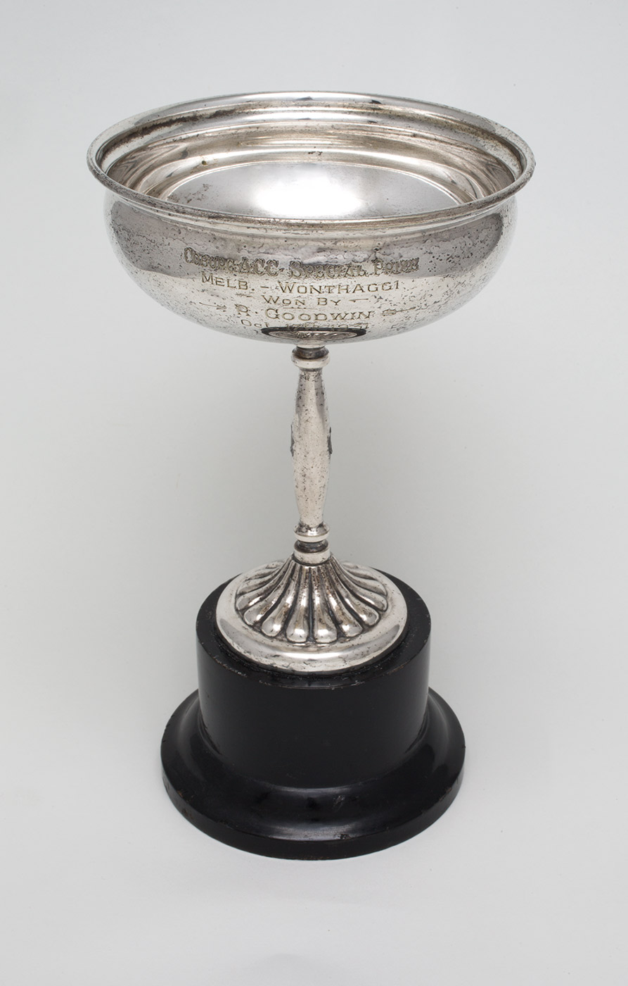 A circular silver presentation cup on a dark timber base. The inscription on the cup partially reads 'COBURG A.C.C. SPECIAL PRIZE / WON BY / R. GOODWIN / Oct 17th 1931'. - click to view larger image