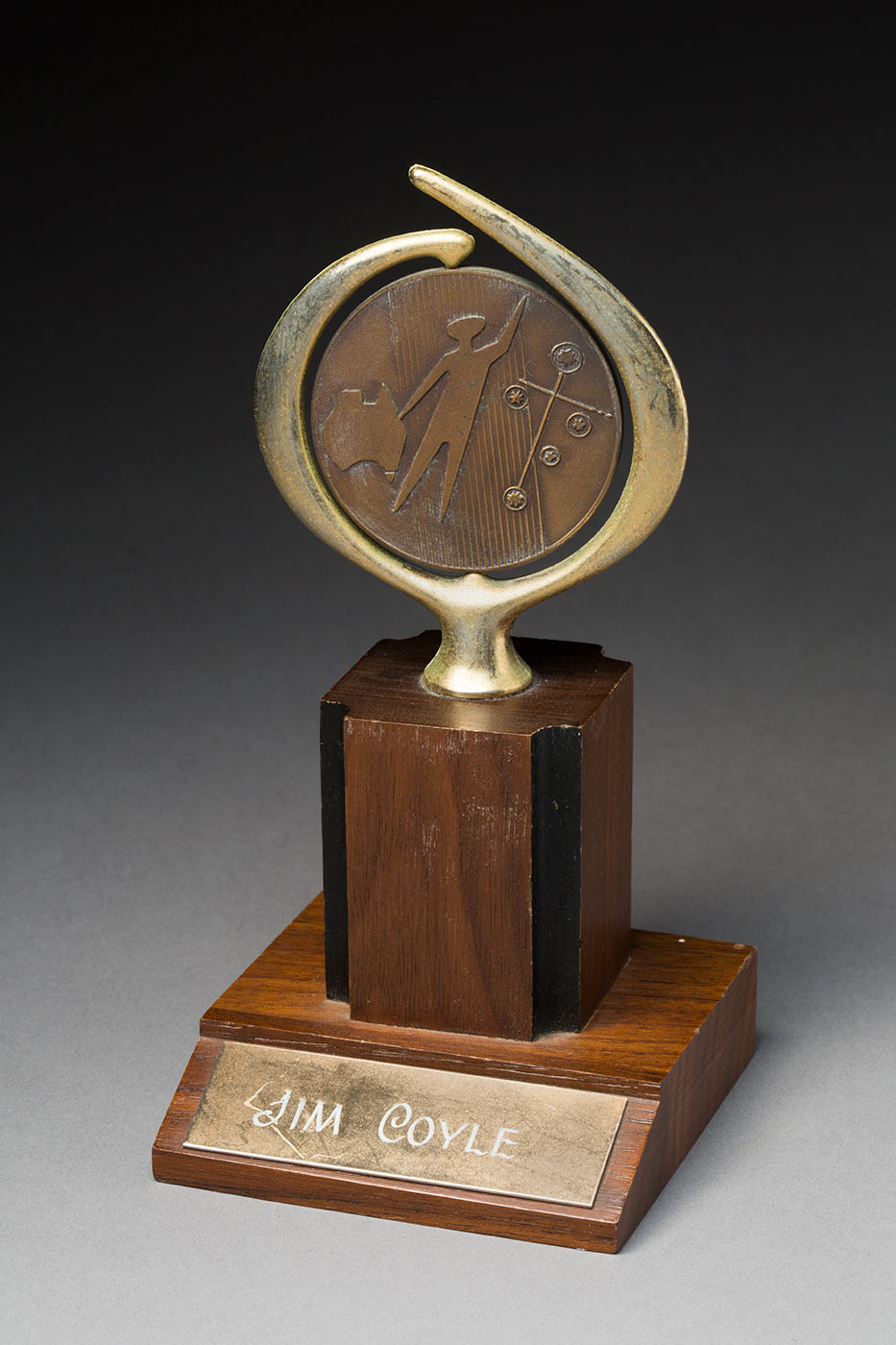 A bronze medallion featuring a stylised image of the shape of Australia, the Southern Cross and a human figure. The Image is encircled by a decorative gold-coloured metal that is support on a wooden pedestal base. Attached to the front of the base is a plaque with inscriptions that read 'JIM COYLE'. There is also inscriptions on the reverse side which read 'AWARDED BY THE AUSTRALIA DAY COUNCIL / FOR/OUTSTANDING / PROWESS / IN THE FIELD / OF SPORT / COMPETED / FOR ON / AUSTRALIA / DAY'. - click to view larger image