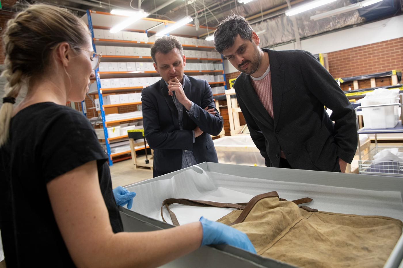 Slava and Leonard Grigoryan inspect an old apron displayed in a conservation box that is presented by a female staff member.