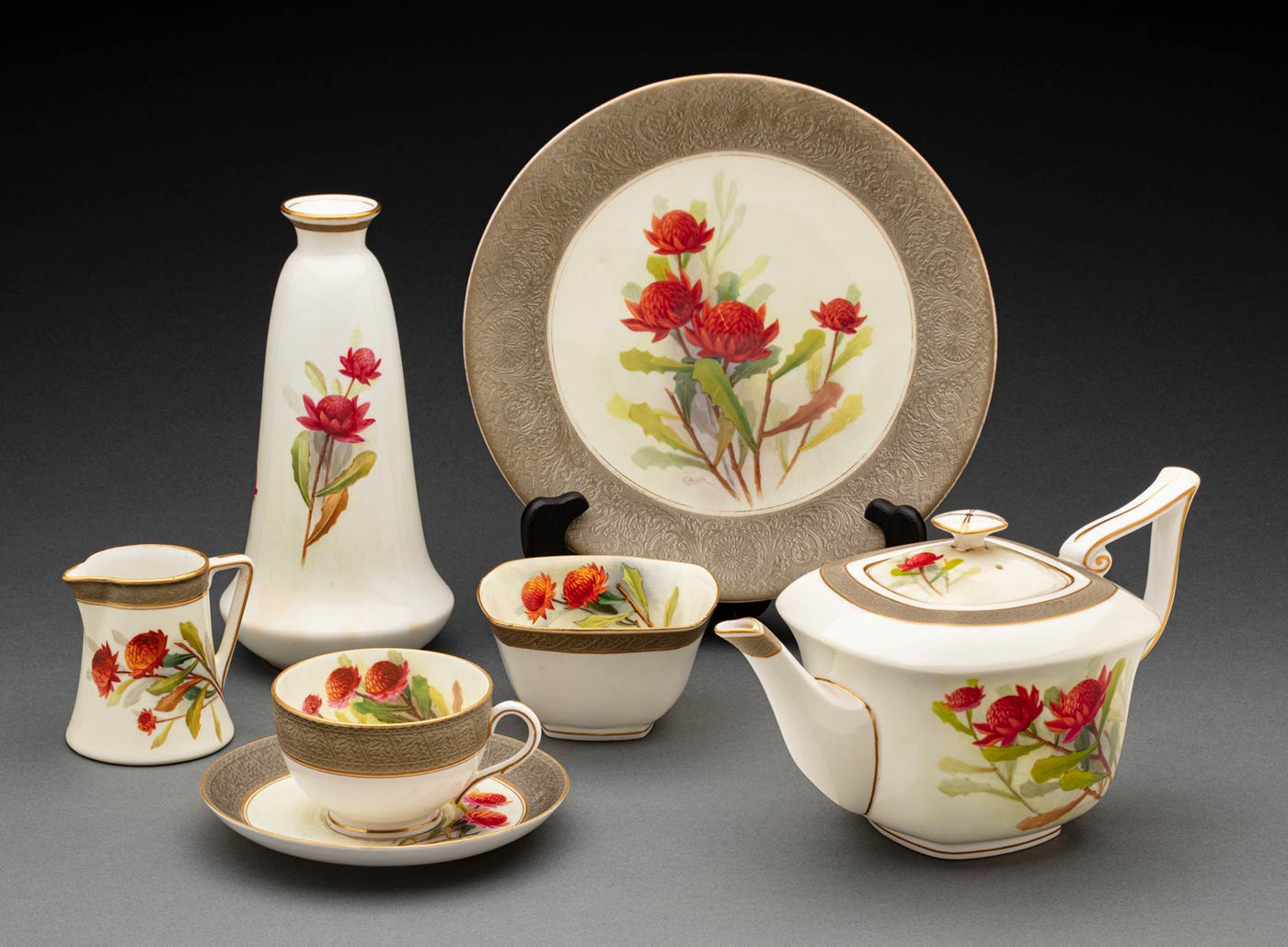 Set of ceramic tableware with detailed embellishments and hand-painted waratahs. - click to view larger image