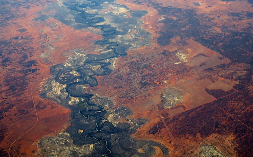 Colour photo of an aerial view of a dry riverbed running through arid landscape.