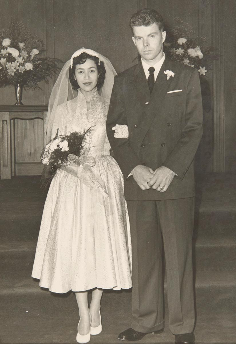 Black-and-white photograph of Yoshiko Ishikawa and Victor Creagh on their wedding day, both facing the camera. Victor stands on the right with his hands clasped at his front, wearing a dark suit. On the left is Yoshiko, holding Victor's arm and a bouquet of flowers. She wears a cream-coloured dress which falls below the knee, light-coloured shoes and a veil. - click to view larger image