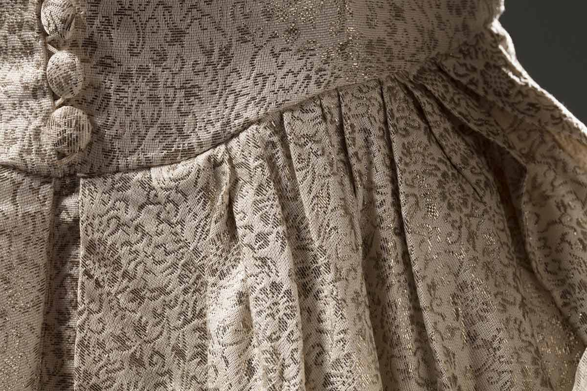 Cropped image of a cream-coloured synthetic brocade dress showing the waistline area. - click to view larger image