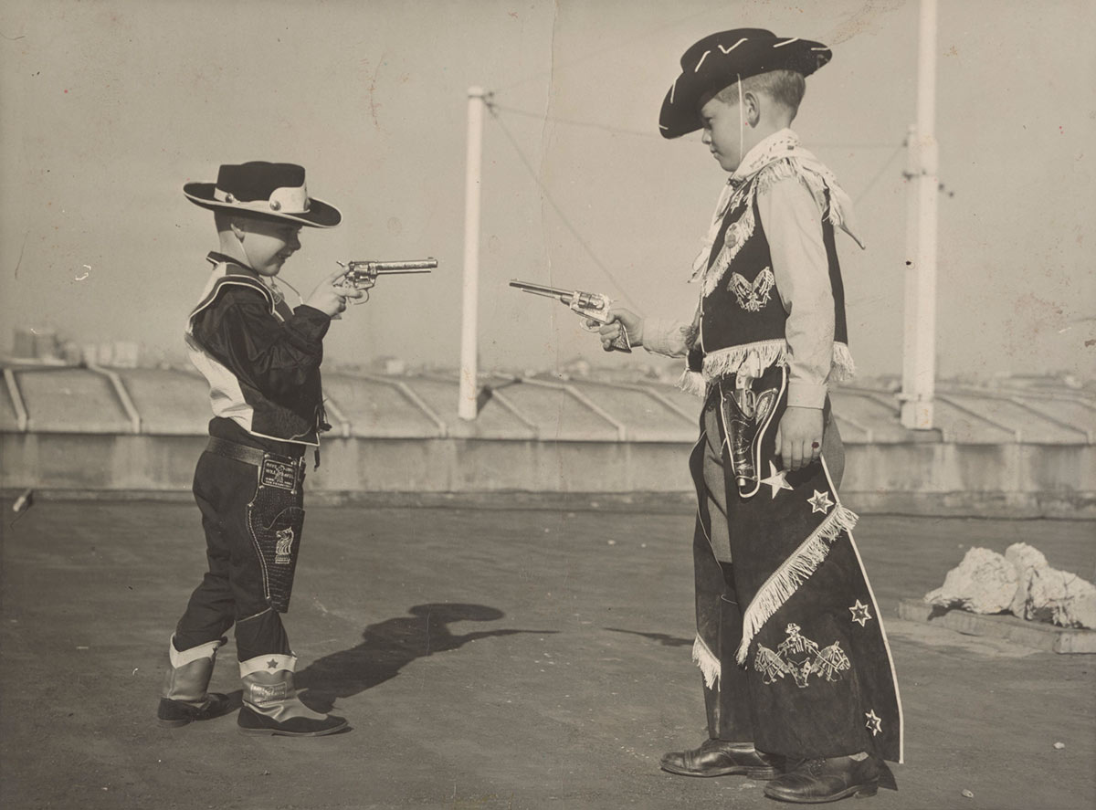 Black and white photograph of two young boys dressed in costumes and pointing toy guns at each other. - click to view larger image