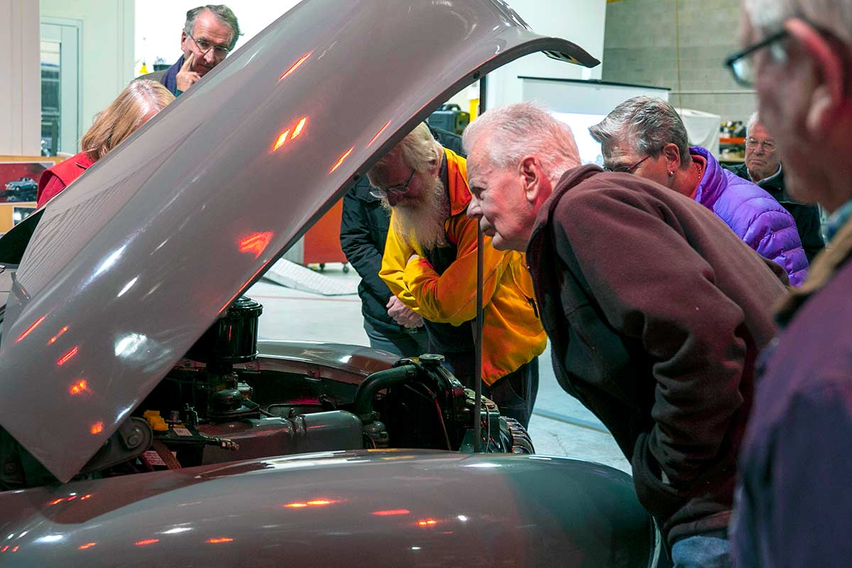 A group of people inspecting the engine of a car. - click to view larger image