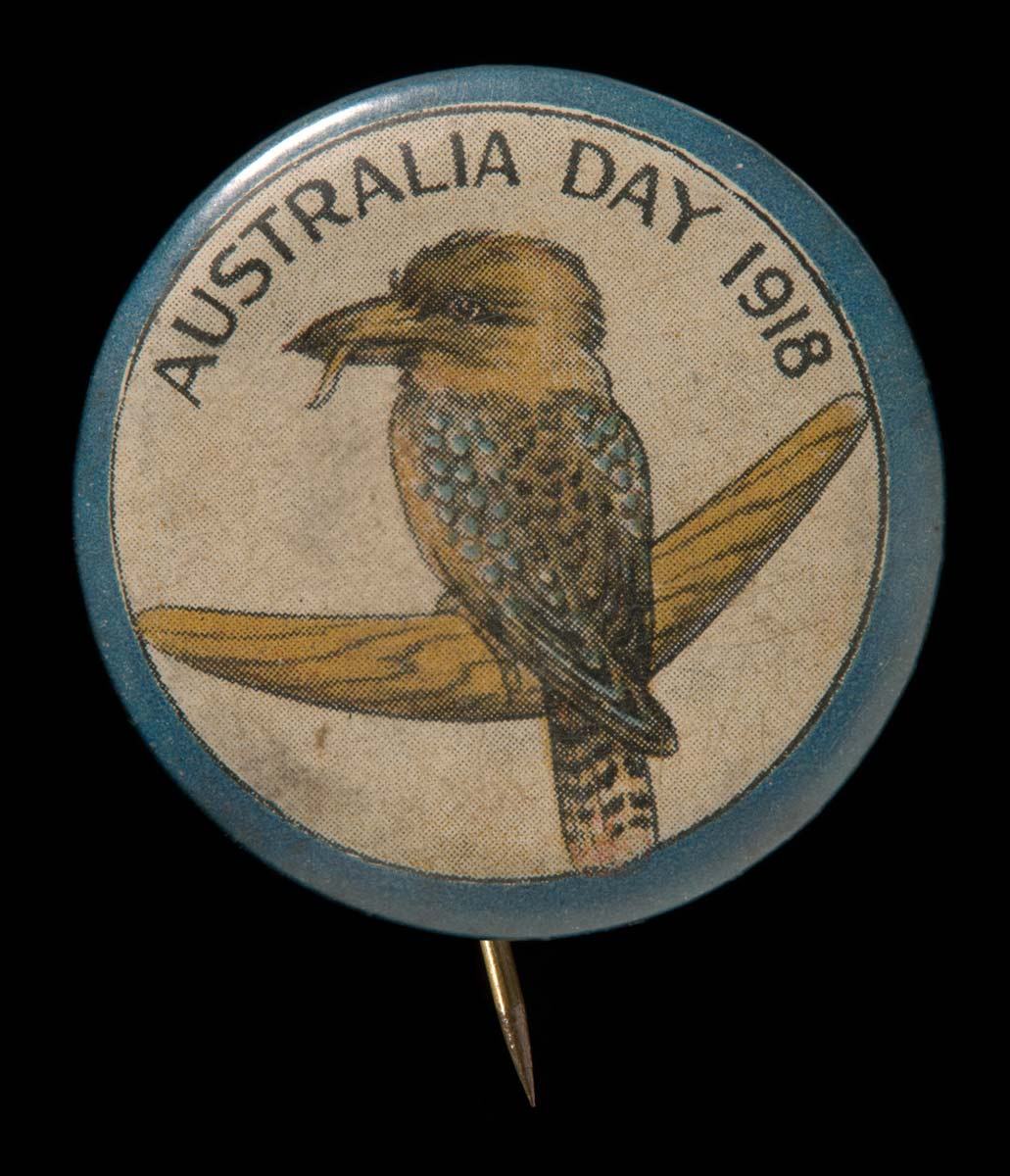 A commemorative circular plastic-coated metal badge. It depicts a brown and blue kookaburra with a worm in its beak, sitting on a brown boomerang, set against a cream background with a blue border.
