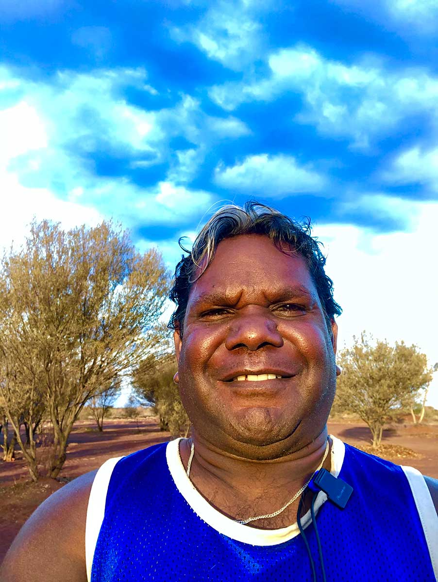 Portrait of a smiling man with the Australian outback in the background. - click to view larger image