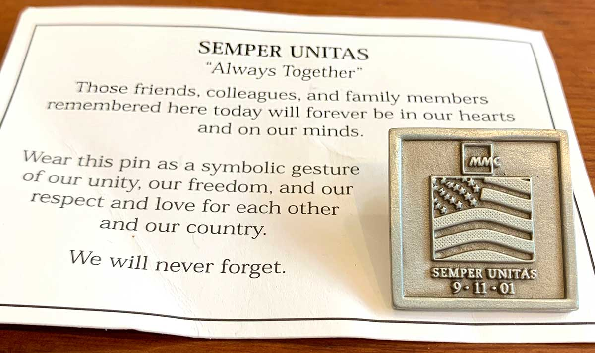 Small square silver pin with engraving of American flag, the letters MMC,  and the words Semper Unitas 9-11-01. The pin is attached to a white card featuring black writing.