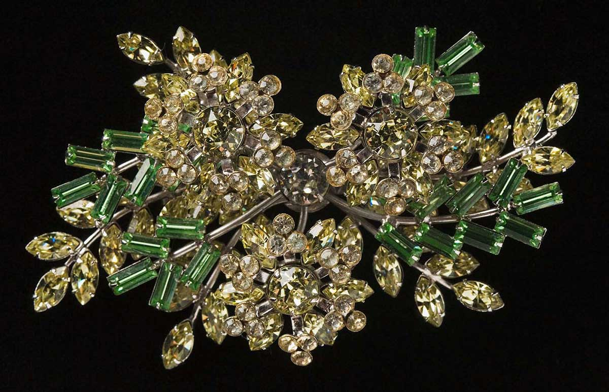 Brooch comprised of yellow plastic wattle blossoms, green leaves and silver-coloured base. - click to view larger image