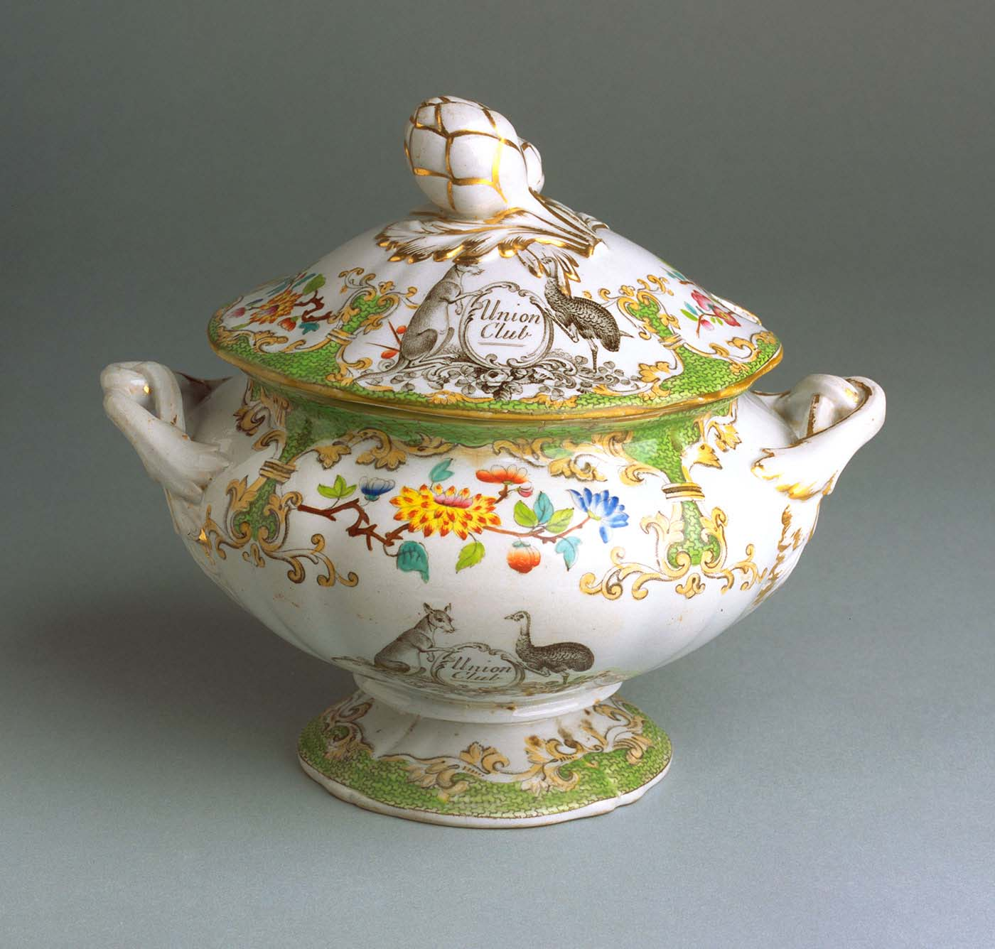 Soup tureen with a white base and gold-rimmed lid and handles. The tureen is adorned with elaborate imagery including flowers and curlicules. A black and white kangaroo and emu appear in a stylised coat of arms with 'Union Club' printed in between. - click to view larger image