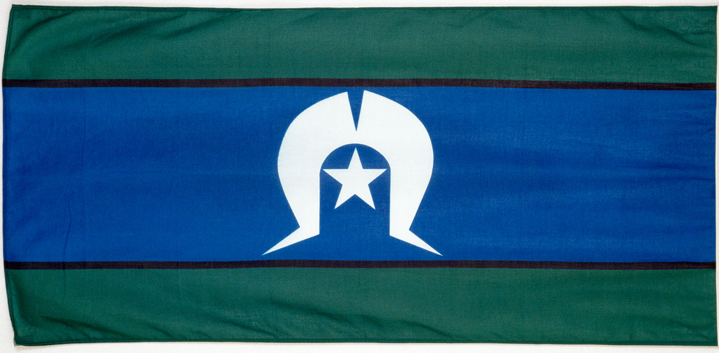 Flag composed of a central blue band, with a white headdress motif and five pointed star, and bordered by green bands top and bottom. - click to view larger image