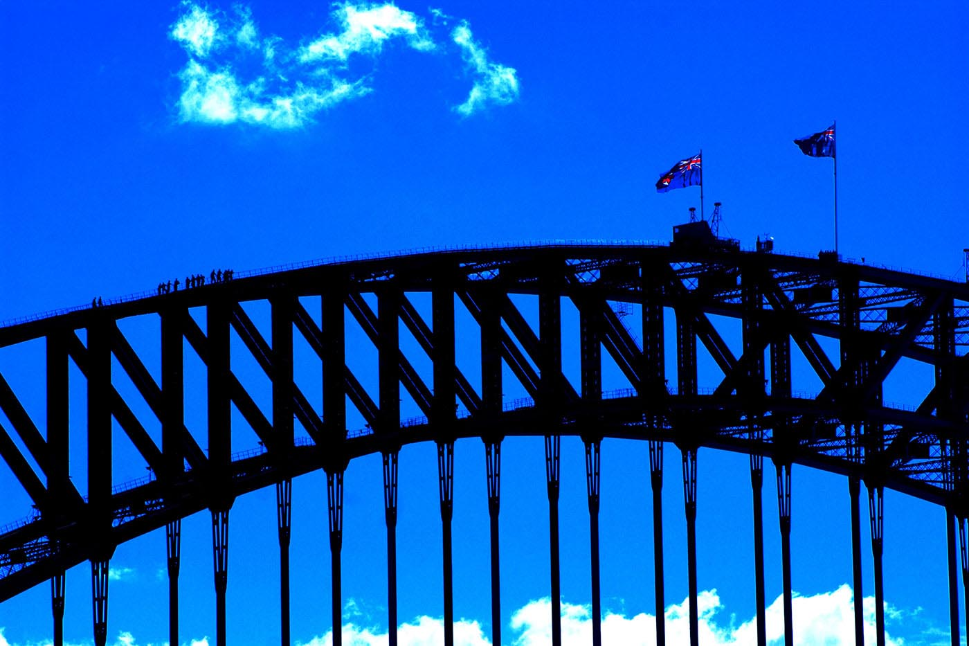 Colour photograph showing the top of the Sydney Harbour Bridge. Two flags fly from the top centre of the arch. A group of climbers, dwarfed by the structure, approach the top of the arch from the left. - click to view larger image