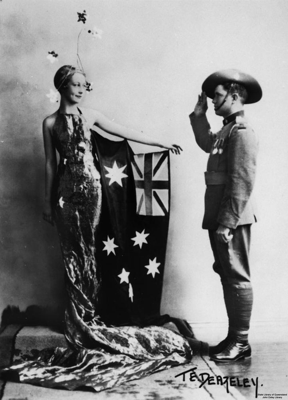 A woman dressed in a sleeveless fitted evening gown, which trails to the floor, wears a headdress of stars. An Australian flag is attached to her left arm, which is extended in the direction of a young man. He wears a soldier's uniform and has his right arm raised in a salute. - click to view larger image