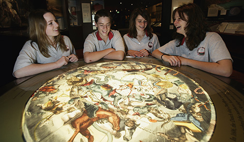 Four students inspect an illuminated map display at the Museum.
