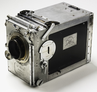 A rectangular box-shaped motion picture camera with a hand-crank and glass lens. The camera's metal body is silver with black side panels and has external slides, levers and dials for adjustment and operation. 'Le Parvo Modele L' is stamped in the metal plate beneath the lens at the front of the camera.
