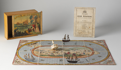 A hand-coloured lithographic playing board made of eight paper sections mounted on linen, with a polygonal twelve-sided teetotum or spinning dice and three small painted metal playing pieces in the shape of tall ships. A varnished wooden box and an instruction sheet have been placed beside the game board.