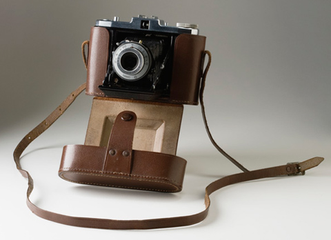 A black camera housed in a brown leather case.