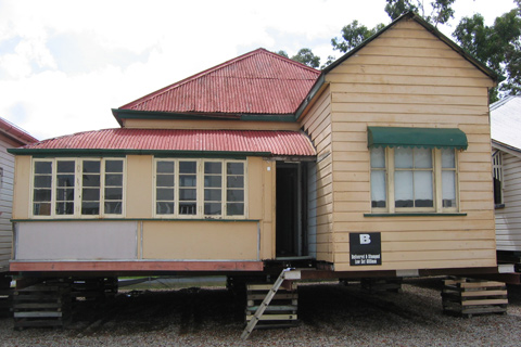 Timber house with a red, corrugated iron roof, raised on wooden supports