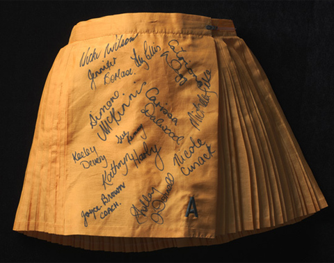 A golden yellow polyester netball skirt. The skirt is pleated, in alternating wide and narrow pleats. The front panel of the skirt is unpleated and signed in black ink by the members of the Australian women's netball team.