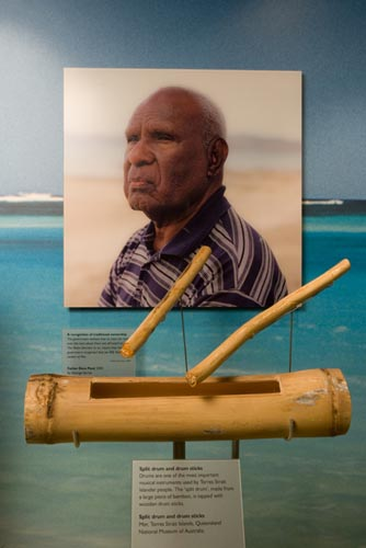 A display that showcases a drum and drum sticks from the Mer region together with an image of one of the three Torres Strait Islander men who fought the Mabo case, Father Dave Passi (2000).