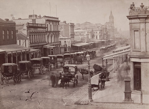 Black and white image of an urban streetscape with a series of two-storey buildings on either side. Many have verandahs at the front and a buildig with a spire rises towards the far end of the street. A series of horse-drawn carriages is lined up along the left side of the street. Another two carriages and several people stand to the right.