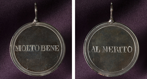 A silver coloured metal disc with a decorative engraved border on both sides. One side of the disc has the words 'MOLTO BENE'. The other side of the disc reads 'Al Merito'. A piece of metal with a hole is attached to the top of the medal to be used for threading on a necklace or similar.