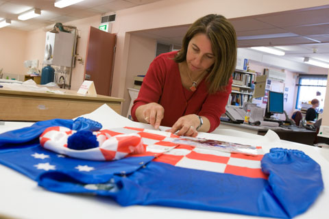 Conservator Carmela Mollica works to reduce the staining on the front of the jockey silks.