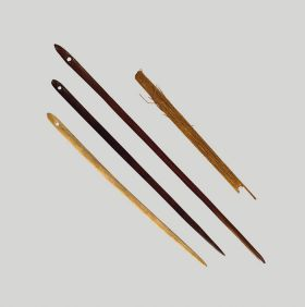 Long wooden needles made of dark brown wood and pointed at the ends with an eye at the wider end.