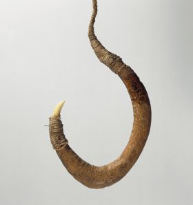 Fishhook with curved wooden shank, bone point, and lashing of twisted cords of plant material.