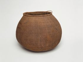 Barrel-shaped basket made of woven coconut leaf ribs, sticks and plant fibre.
