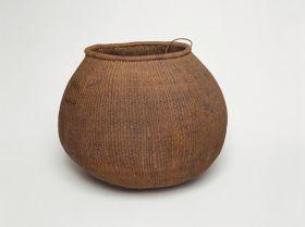 Barrel-shaped basket made of woven coconut leaf ribs, sticks and plant fibre.