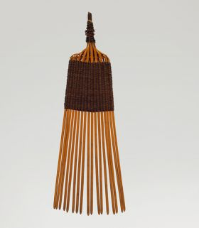 A comb made of seventeen small sticks woven together with a 4cm long weave made of light brown and black fibres.