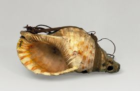 Shell trumpet, made from the shell of the species Triton tritonis, has a blowhole on one side, directly underneath the tip.  It has a fibre band attached like a handle.