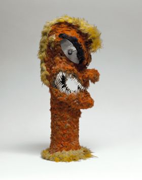 Feathered idol with the shape of a human figure, formed of wicker-work, overlaid with feathers of red, yellow and black.  The eyes are mother-of-pearl and the mouth fitted with dog-teeth.