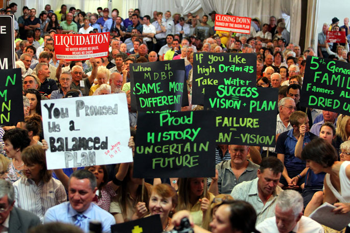 Colour photograph showing a room crowded with people. Some of the people hold protest signs above their heads.