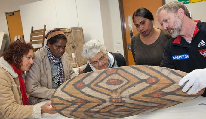 Visitors from Far North Queensland with curator David Kaus examining a shield